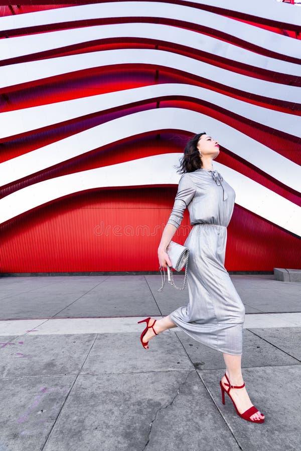 En vacker flicka i en silverklänning i en berömd byggnad arkivfoton
