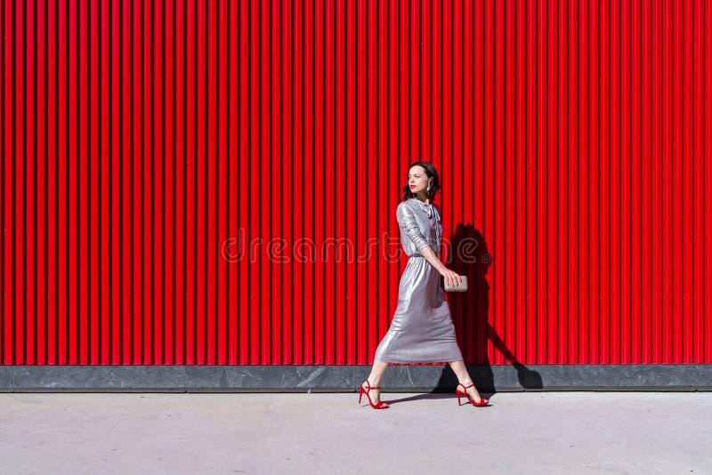 En vacker flicka i en silverklänning utomhus royaltyfri foto
