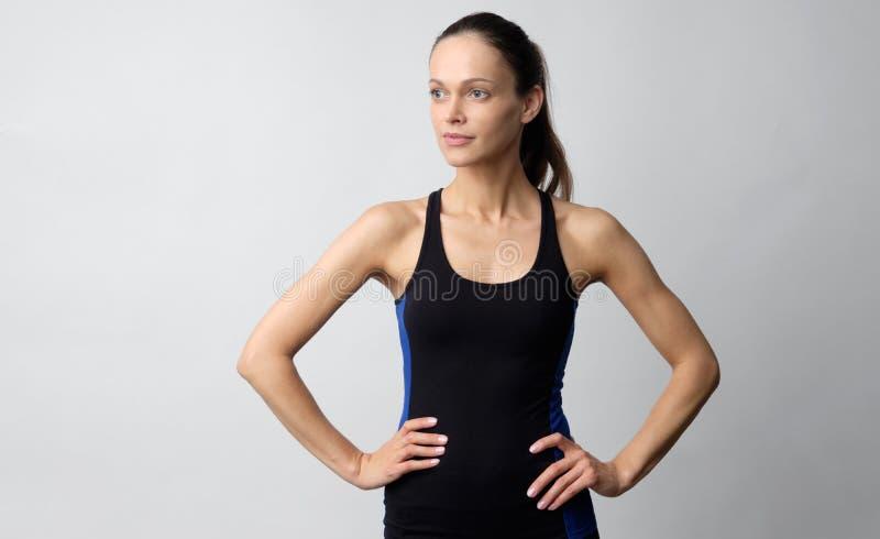 En vacker kvinna bär idrottskläder isolerade på grå bakgrund royaltyfri fotografi