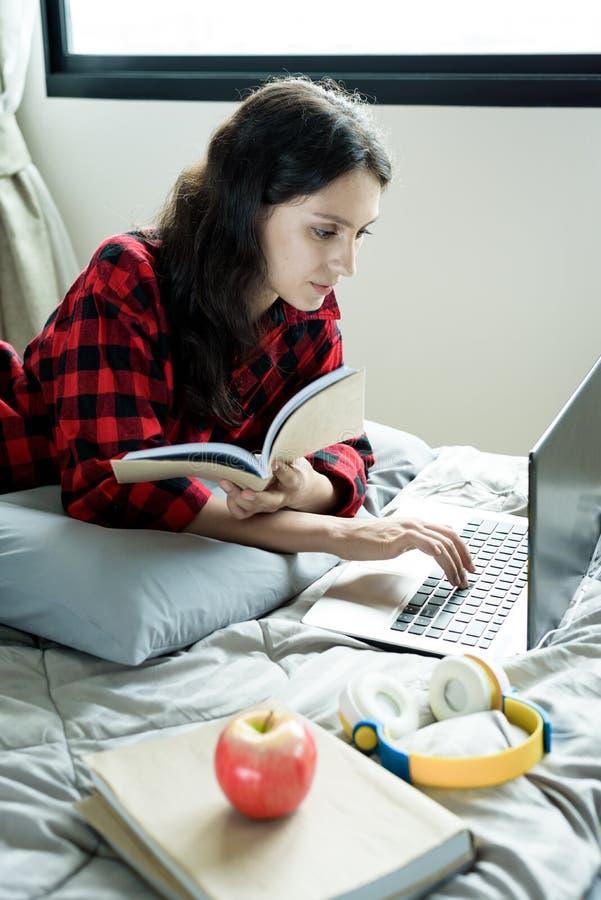 En vacker kvinna som arbetar och läser en bok på en bärbar dator och som ligger på sängen på en kondominium på morgonen arkivbild