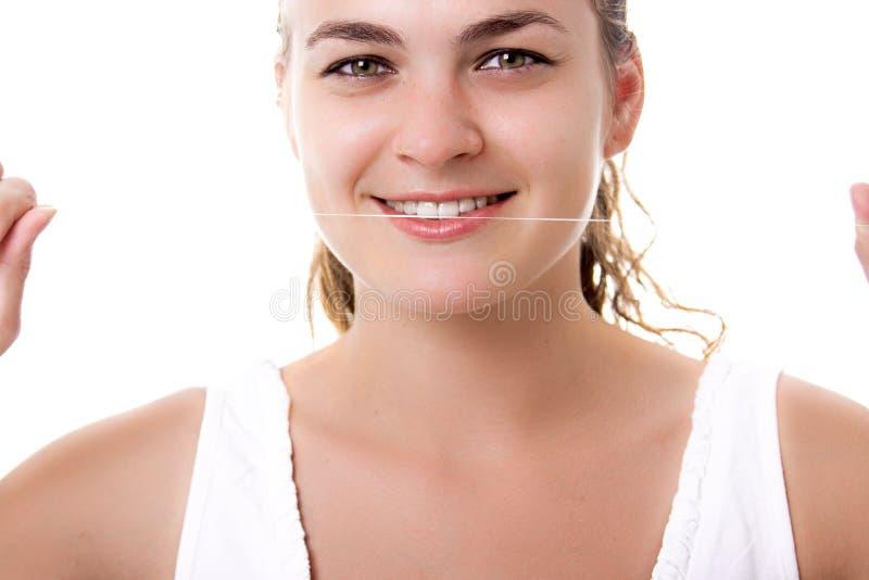 En vacker kvinna som håller en tandtråd för att få henne att tappa tåget arkivbilder