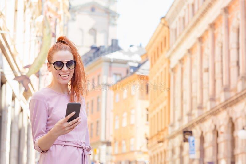 En vacker kvinna som står på gatan och använder sin mobiltelefon royaltyfri fotografi