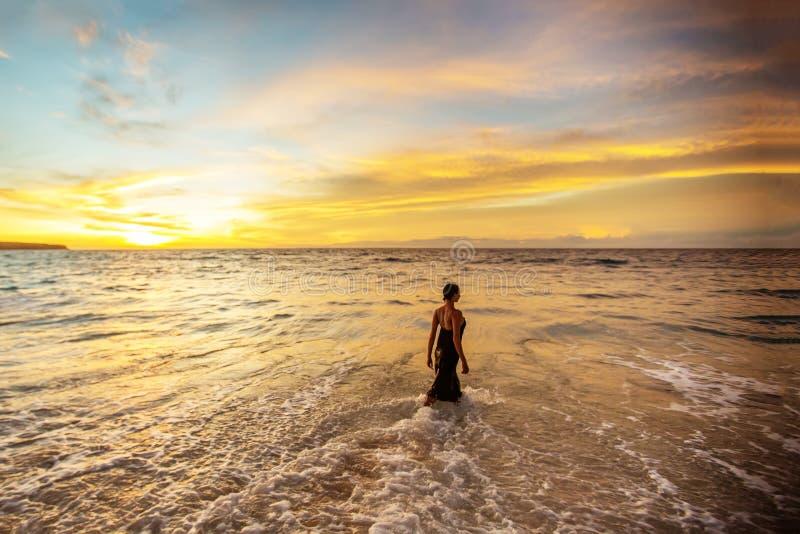 En vacker kvinna vid havet vid solnedgången royaltyfri fotografi