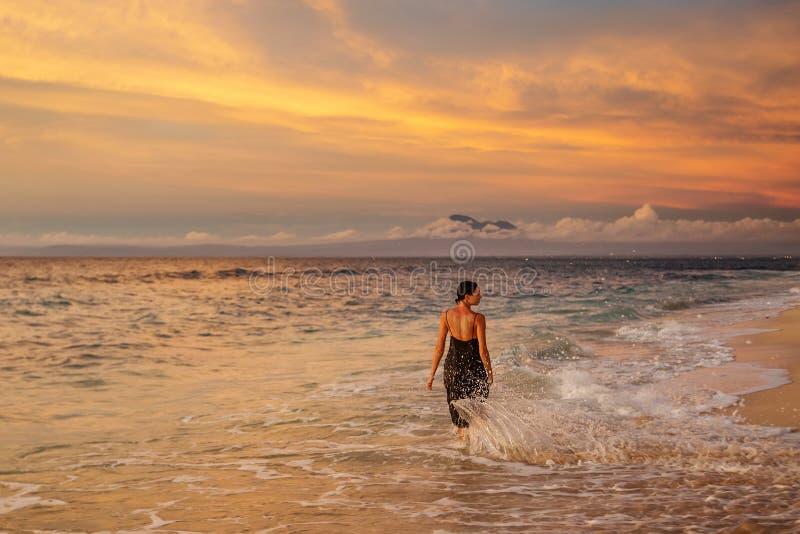 En vacker kvinna vid havet vid solnedgången arkivfoton