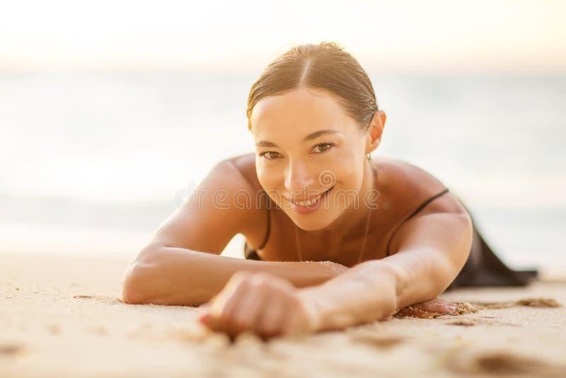 En vacker kvinna vid havet vid solnedgången royaltyfri bild