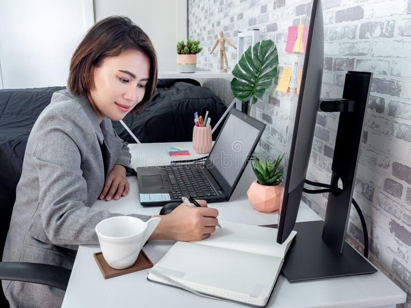 En vacker, lycklig asiatisk kvinna som arbetar med en bärbar dator i sitt rum, kondominium royaltyfria bilder