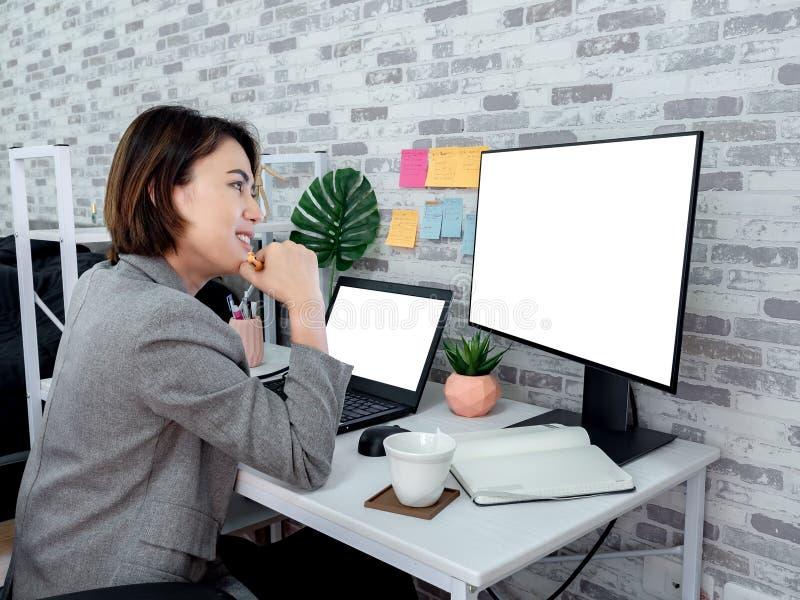 En vacker, lycklig asiatisk kvinna som arbetar med en bärbar dator i sitt rum, kondominium royaltyfri foto