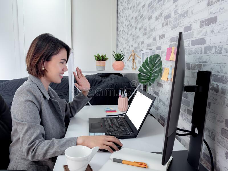 En vacker, lycklig asiatisk kvinna som arbetar med en bärbar dator i sitt rum, kondominium royaltyfria foton