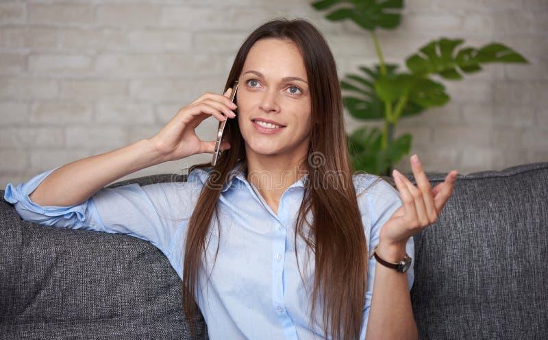 En vacker tjej pratar på telefon hemma fotografering för bildbyråer
