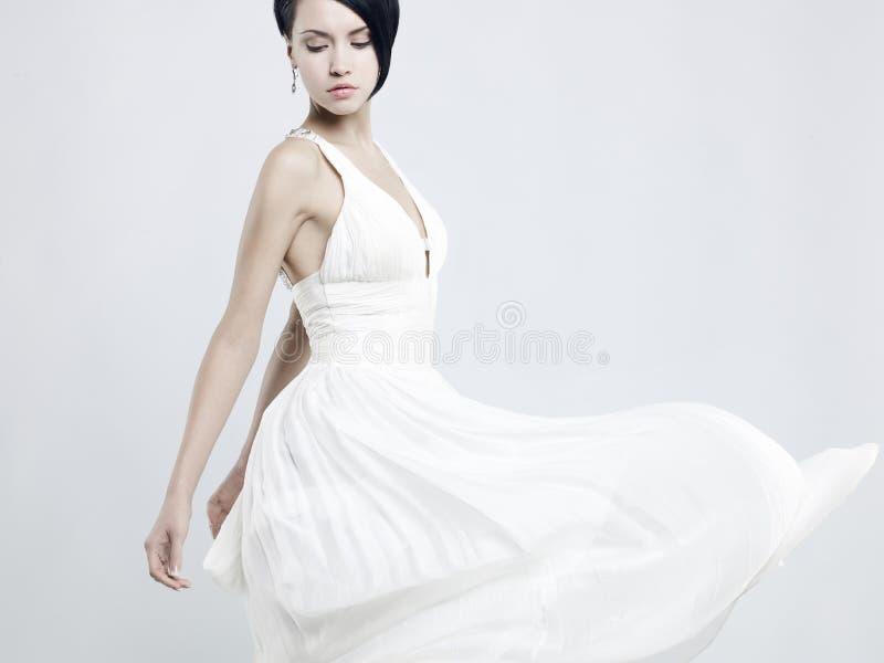 En vacker ung dam i en fakturerande vit klänning arkivfoton