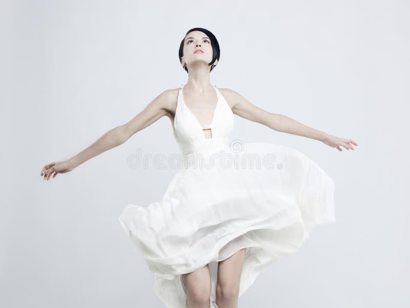En vacker ung dam i en fakturerande vit klänning royaltyfri fotografi