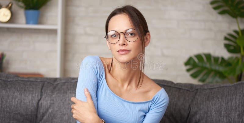 En vacker ung flicka i ögonglasen sitter på en soffa royaltyfri foto