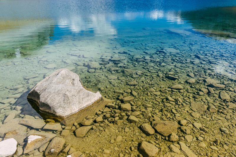 En vagga i en sjö med genomskinligt blått vatten i de franska fjällängarna arkivfoto