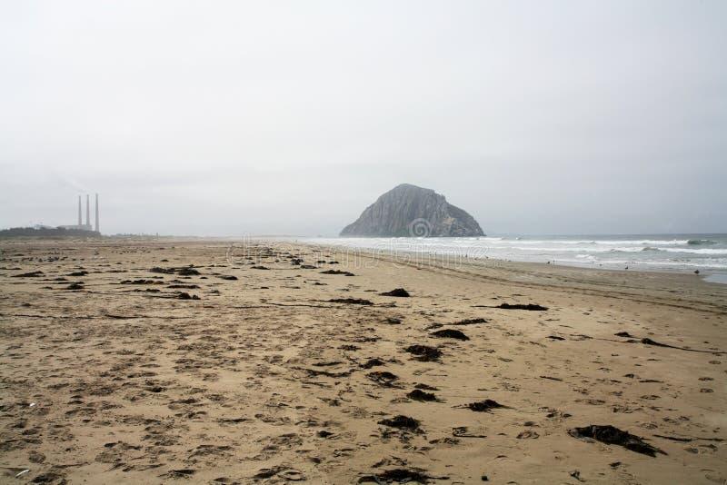 En vaggaklippa i havet across från rökbuntar arkivbilder
