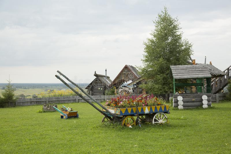 En vagn, en väl och liten vagn på en grön gräsmatta royaltyfri fotografi
