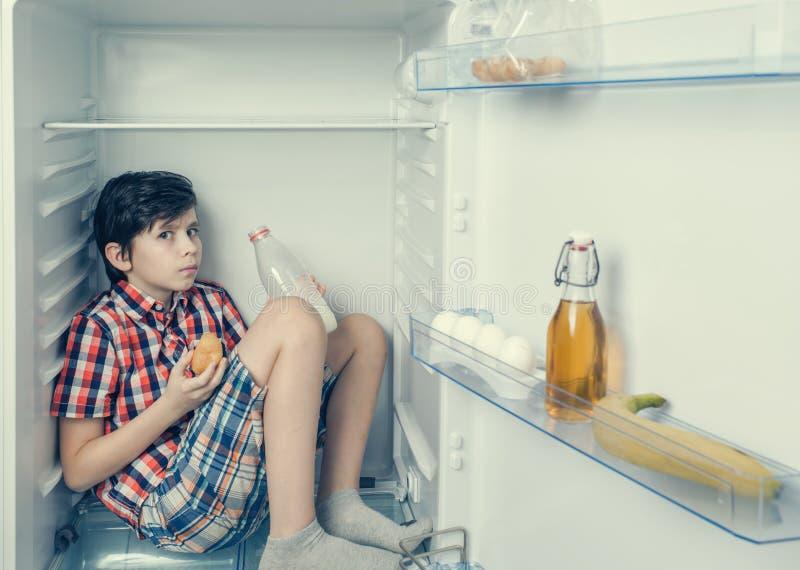En vaken pojke i en skjorta och kortslutningar som äter en giffel och en drink, mjölkar inom en kyl med mat och produkten Närbild arkivfoto