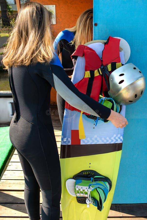 En vaklogiflicka samlar utrustning - en wakeboard, kängor, en hjälm och en wakesurfing väst arkivfoto