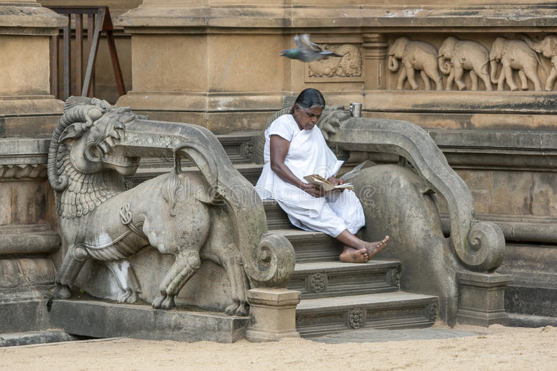 En vallfärda till Kelaniyaen Raja Maha Vihara nära Colombo i Sri Lanka sitter på momenten till relikskrinrummet royaltyfri bild