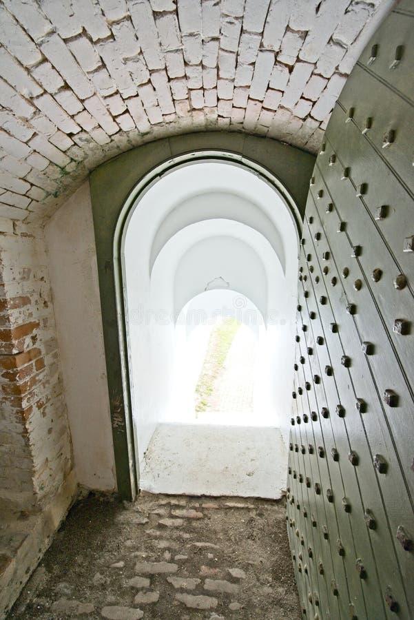 En valvgångutgångsdörr som inneslutas i en historisk tegelstenbyggnad royaltyfria bilder