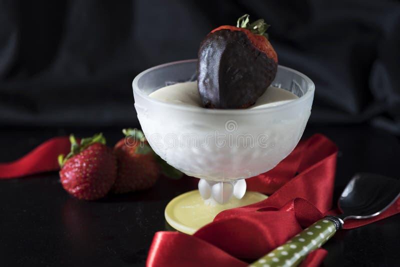 En vaniljsåsbunke med choklad doppade jordgubben, och en grön polka prack upp skeden på en svart bakgrund, slut royaltyfri bild