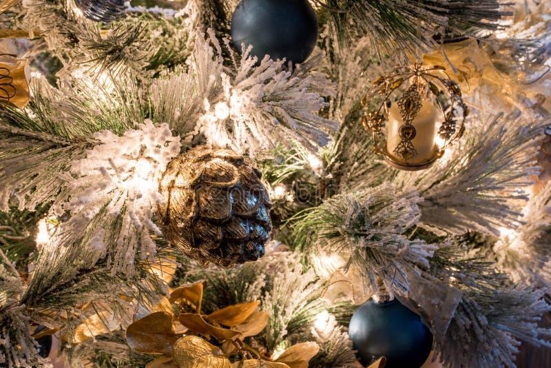 En variation av blåa och guld- julprydnader på en flockas julgran royaltyfria bilder