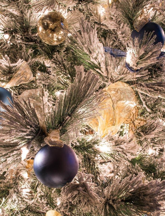 En variation av blåa och guld- julprydnader på en flockas julgran arkivfoto