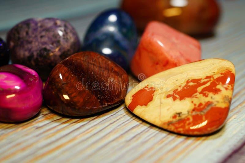 En variation av halv-dyrbara stenar av olika mineraler och strukturer på en trätabell En samling av polerat olikt arkivfoton
