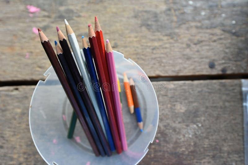 En variation av kulöra blyertspennor i klara plast- askar arkivfoto