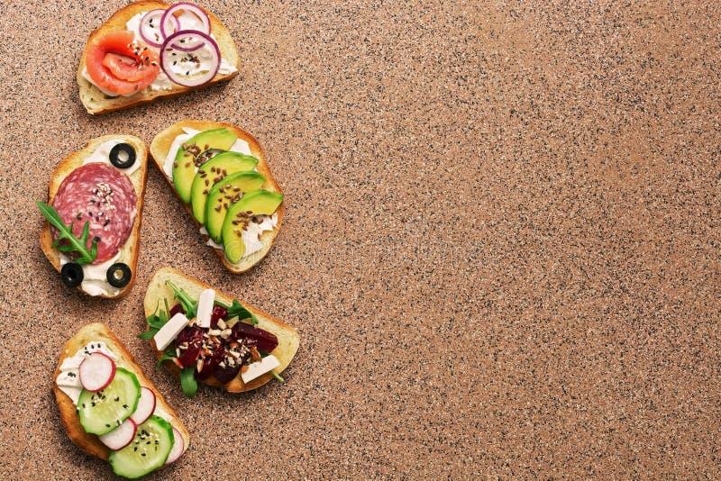 En variation av smörgåsar med den röda fisken, rökt korv, grönsak på en bruntstenbakgrund Bästa sikt, kopieringsutrymme fotografering för bildbyråer