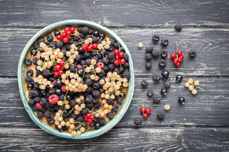 En variation av vinbärbär gulnar och röda, svarta och röda hallon, på en lantlig keramisk maträtt, den trägamla tabellen Sikten f royaltyfria bilder