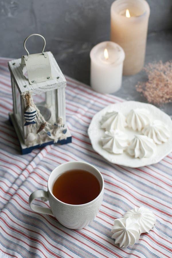 En varm kopp av svart te med en platta av luftiga marängar på en randig bordduk, en dekorativ sjöstjärna och en lykta, vaxstearin arkivfoton