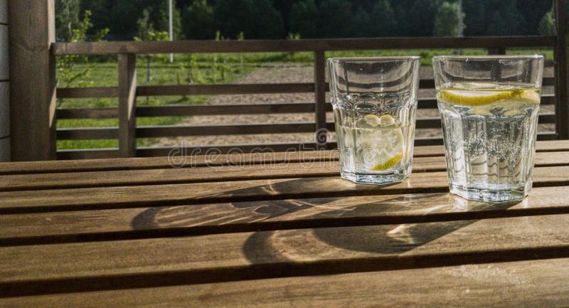 En varm sommardag i byn, utomhus- rekreation för sommar På tabellen är två exponeringsglas av klart exponeringsglas med förnyande royaltyfri bild