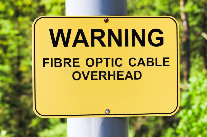 En varningsfiber - över huvudet tecken för optisk kabel arkivfoton
