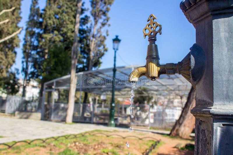 En vattenkran med en vattendroppe Begrepp för vattenförbrukning utanför royaltyfri bild