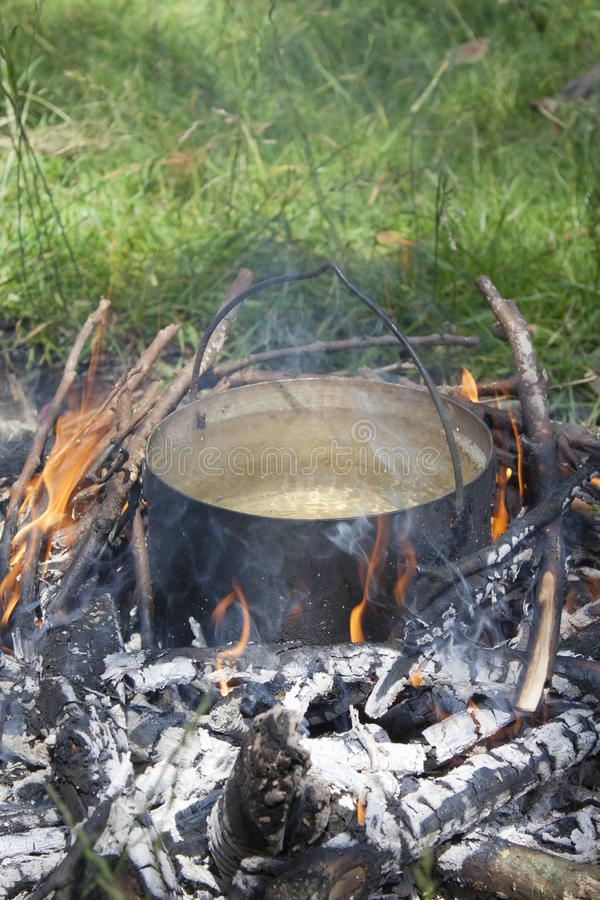 En vattenkruka värms upp på en brand av grenar royaltyfri bild