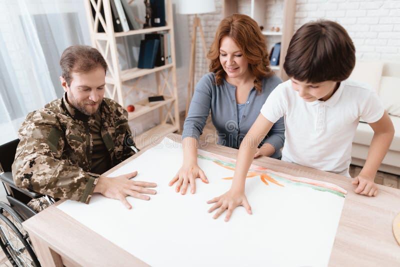 En veteran i militär likformig i en rullstol spenderar tid med hans familj Familjen drar tillsammans royaltyfria bilder