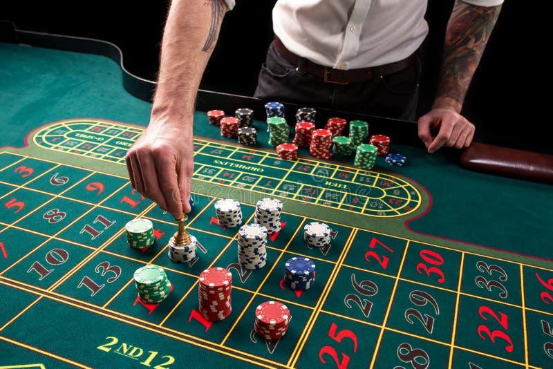 En vibrerande bild för närbild av den gröna kasinotabellen med rouletten, med händerna av croupier och mångfärgade chiper arkivbilder