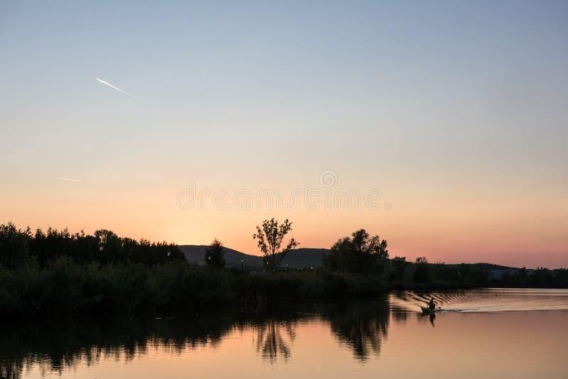 En vibrerande solnedgång över den sjön en anonym man hänger i th arkivfoto