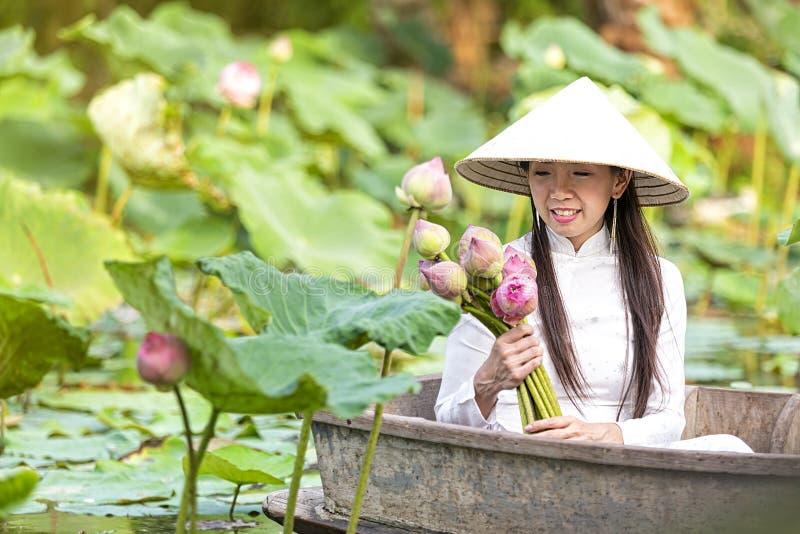 En vietnamesisk kvinna sitter på ett träfartyg och samlar rosa lotusblommablommor Kvinnlig rodd på sjöskördnäckrors arkivbilder