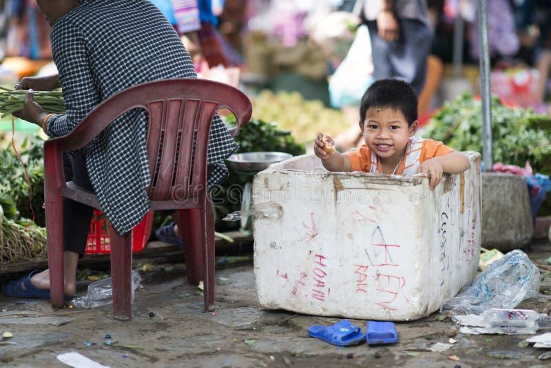 En vietnamesisk unge som spelar i en polystyrenask i Bac Ha Market, Lao Cai, Sapa, Vietnam royaltyfri foto