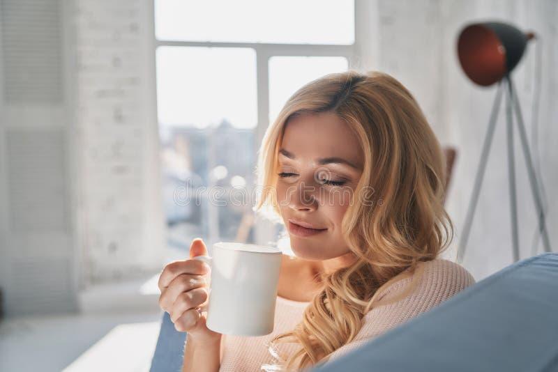 En vilken lukt! Attraktiv ung kvinna som rymmer en kopp och håller e royaltyfri bild