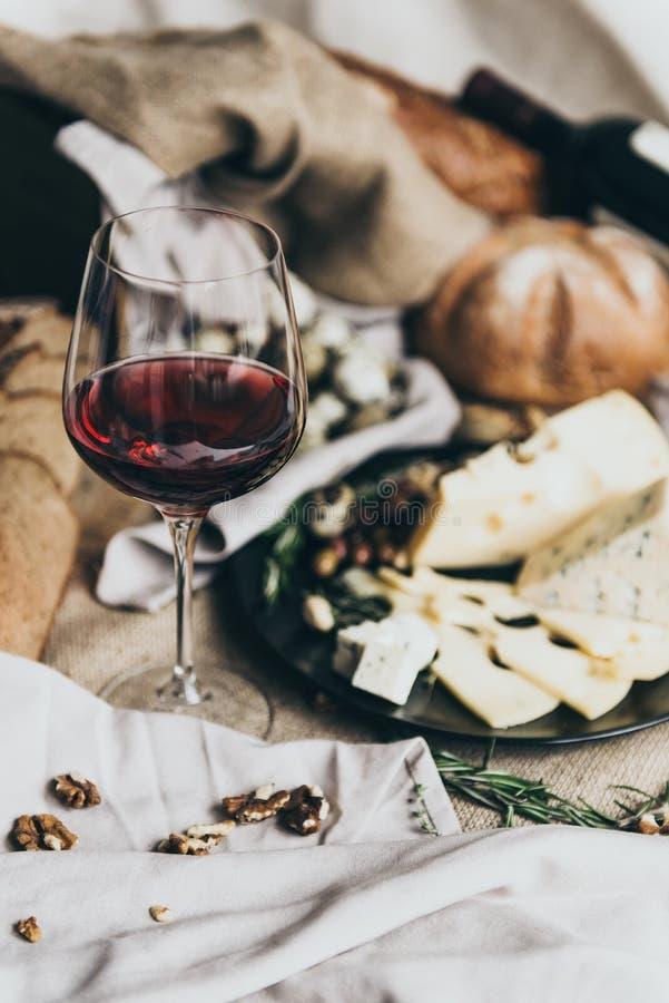 En vinglas fylls med torrt rött vin som bakom ligger Nytt bröd, ädelost, masdaamost, vaktelägg och muttrar är arkivbild