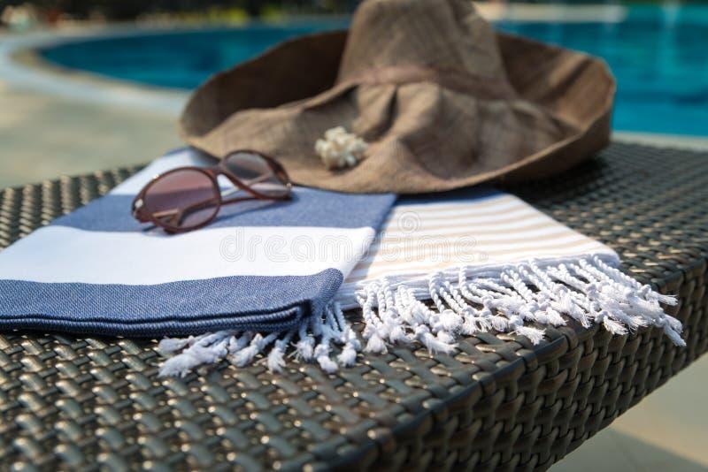 En vit, blått och en beige turkisk handduk, en solglasögon och en sugrörhatt på rottingdagdrivare med den blåa simbassängen som b royaltyfria bilder