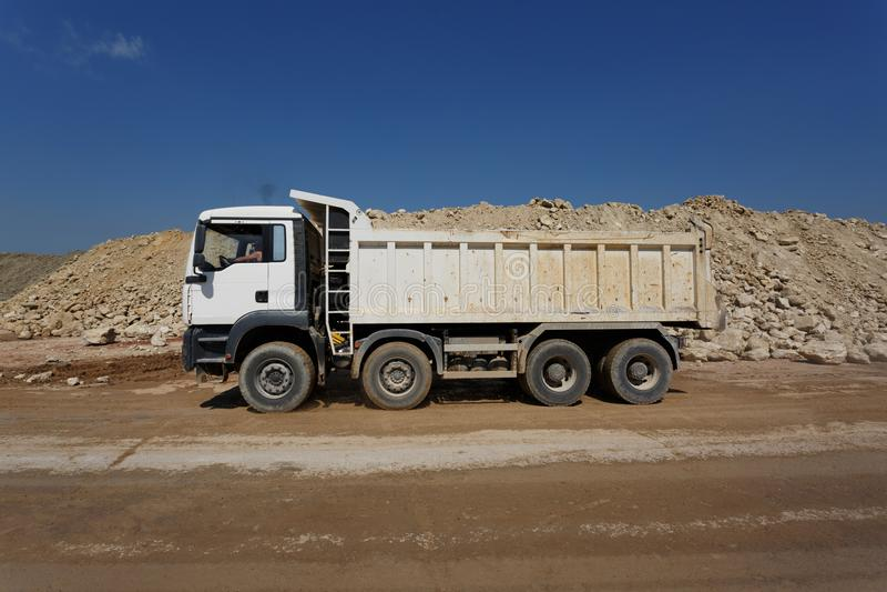 En vit dumper, lastbil mycket av stenar i ett sandvillebråd, transportering av material på en naturlig bakgrund royaltyfri foto