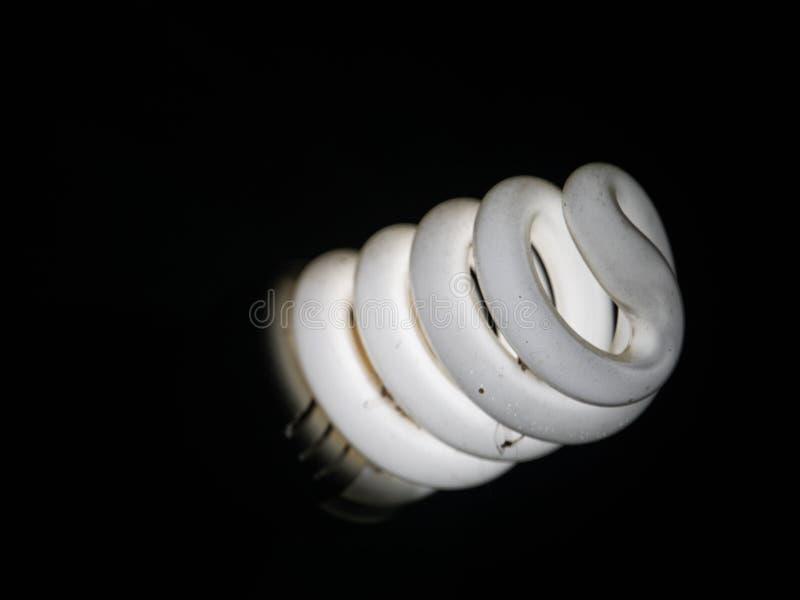 En vit energi - sparande kula och sv?rtad bakgrund arkivbilder
