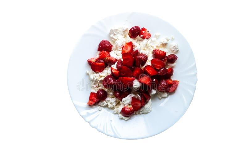 En vit enkel platta med keso och skivade saftiga jordgubbar, vitt som isoleras arkivbild