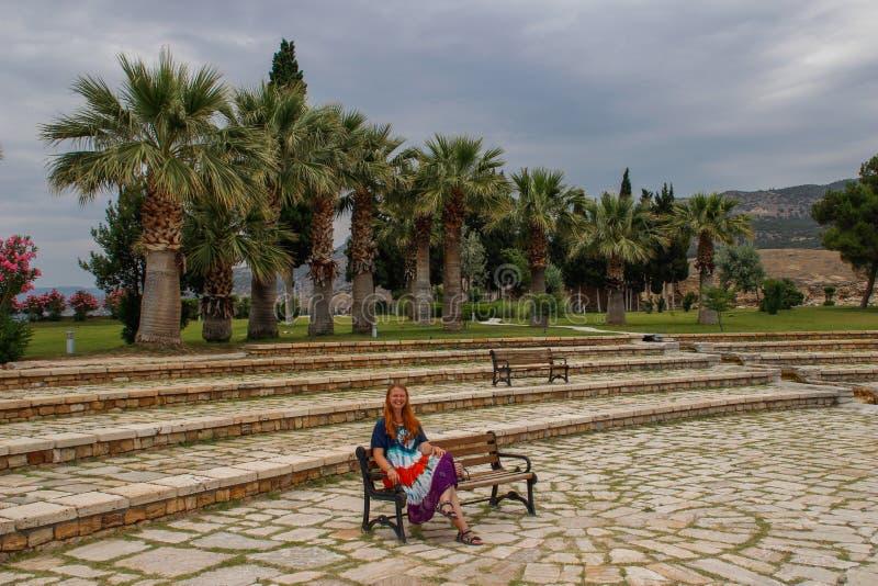 En vit flicka i en hippieklänning sitter och vilar på en bänk i den Pamukkale nationalparken arkivfoton