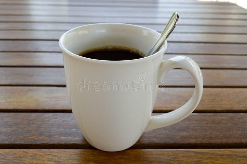 En vit keramisk kopp med ett uppfriskande varmt kaffe för morgon med tedrinken och den skinande teskeden för te är på en trätabel arkivbilder
