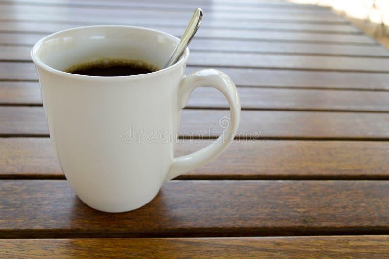 En vit keramisk kopp med ett uppfriskande varmt kaffe för morgon med tedrinken och den skinande teskeden för te är på en trätabel arkivfoto