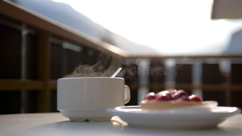 En vit kopp av den varma drinken och en platta med efterrätten på kafét royaltyfria foton